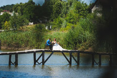 Wedding Picnic on Bridge. Newlyweds having picnic on wooden bridge Royalty Free Stock Photos