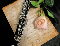 Retro old clarinet. Wedding picture with a clarinet and a rose on the background of notes royalty free stock image
