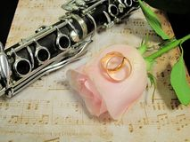 Retro old clarinet. Wedding picture with a clarinet and a rose on the background of notes stock image