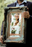 Wedding picture, elegant bride throw antique mirror Royalty Free Stock Image