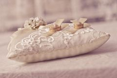 Wedding pillow. A wite wedding pillow with two gold rings lying on the table Royalty Free Stock Image