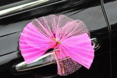 Wedding pink bowknot. Pink ribbon bowknot on wedding car door handle stock images