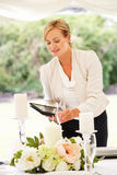 Wedding Planner Checking Table Decorations In Marquee. Smiling royalty free stock photography