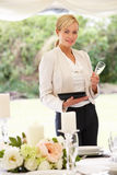 Wedding Planner Checking Table Decorations In Marquee. And Smiling To Camera Royalty Free Stock Photo