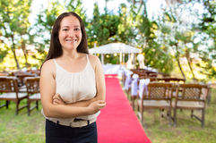 Wedding planner smiling. Wedding planner woman is organizing the wedding reception venue for her customers standing and smiling at the wedding place stock photos