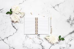 Marble table flat lay with open notebook and pen for wedding planning, bloggers, students, office Stock Photo