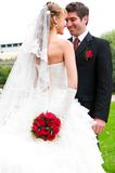 Wedding portrait. Bride is hiding her wedding bouquet from groom Royalty Free Stock Images