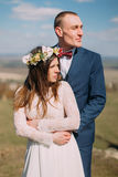 Wedding portrait of happy stylish newlywed bride and groom hugging outdoor with cloudy sky at background Royalty Free Stock Image