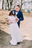 Wedding portrait of happy stylish newlywed bride and groom posing outdoor with leafless trees at background Stock Photos