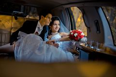 Wedding portrait. Happy young stylishly dressed couple is sitting in the car and looking through window. The bride with. The wedding bouquet of red roses and Royalty Free Stock Images