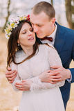 Wedding portrait of stylish newlywed bride and groom happily embracing outdoor with leafless trees at background Royalty Free Stock Photography