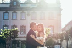 Wedding portrait in the sun. The groom is kissing the charming brunette bride with pretty smile in the town street. Wedding portrait in the sun. The groom is Royalty Free Stock Images