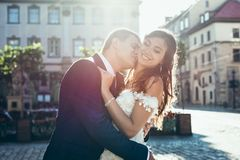 Wedding portrait in the sun of the handsome groom kissing the beautiful smiling brunette bride in the neck. Wedding portrait in the sun of the handsome groom Royalty Free Stock Images