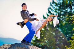 Wedding portraits. A just married couple, on a stone, in the mountains royalty free stock image