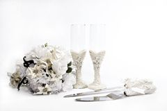 Wedding preparation. Isolated shot of wedding paraphernalia showing bouquet, wine glass, cutlery on a white background royalty free stock image