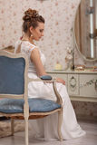 Wedding preparation. Beautiful young bride in white wedding dress indoors. Luxury model sitting on vintage blue chair at home in s Stock Photos