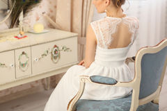 Wedding preparation. Beautiful young bride in white wedding dress indoors. Luxury model sitting on vintage chair at home in studio Stock Photography
