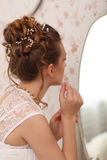 Wedding preparation. Beautiful young bride in white wedding dress indoors. Luxuty model looking at mirror and put on earring, at h Royalty Free Stock Photography