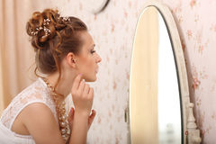 Wedding preparation. Beautiful young bride in white wedding dress indoors. Luxuty model looking at mirror and put on earring, at h Royalty Free Stock Photos