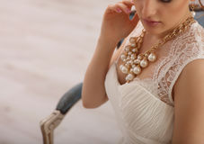 Wedding preparation. Beautiful young bride in white wedding dress and perls indoors. Luxury model sitting on vintage chair at home. Portrait of beautiful bride Stock Photography