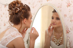Wedding preparation. bride in white wedding dress indoors. Luxuty model looking at mirror and put on earring, at home, in studio r Royalty Free Stock Photo
