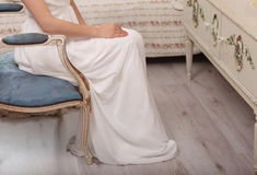 Wedding preparation. bride in white wedding dress indoors. model sitting on vintage blue chair at home in studio room with big win Stock Photos