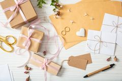 Flat lay and top view of presents and wedding invitations on a white wooden tabletop, background