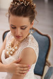 Wedding preparation indoors. Luxury model sitting on vintage chair at home in studio Royalty Free Stock Photo