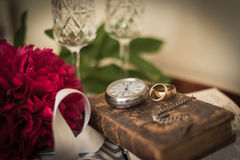 Wedding Preparations. Artistic still-life illustrating a wedding-day, with champagne, wedding rings, watch, button-hole flower and bible Stock Photos