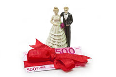 Wedding present. Bridal couple and  fivehundred Euro banknote wrapped with red ribbon as a gift Stock Photos