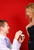 Wedding proposal. A man proposing marriage to her girlfriend, who is astonished. Studio shoot over red background. Vertical color image Stock Image