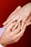 Wedding proposal. Man putting an engagement ring on a woman's hand over red background. Vertical color image Stock Image