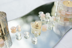 Wedding Reception Candle Centerpieces. A romantic garden wedding reception head table with heart candles and mirror. Horizontal orientation Royalty Free Stock Photography