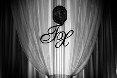 Wedding reception decoration: initials and icon on white curtain Stock Image
