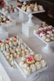 Wedding reception dessert table with delicious decorated white c. Upcakes with frosting closeup royalty free stock image
