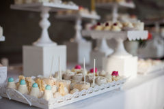 Wedding reception dessert table with delicious decorated white c. Upcakes with frosting closeup stock photography