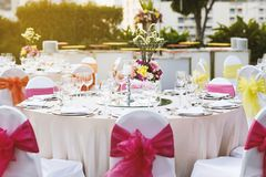 Wedding reception dinner table setting with flower decoration and white cover chairs pink sash. Warm sunset light with wedding reception dinner table setting Stock Photo