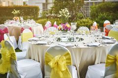 Wedding reception dinner table setting with flower decoration and white cover chairs yellow sash. Wedding reception dinner table setting with empty glasses of Royalty Free Stock Images