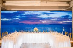 Wedding reception dinner table setting during sunset with ocean view background royalty free stock photos