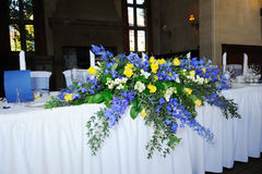 Wedding Reception Flowers. Blue and yellow flowers on top table Stock Photos