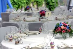 Wedding reception laid tables. Close up of beautifully laid tables at wedding reception venue, focus on bouquet of flowers Stock Photo