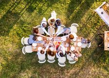 Wedding reception outside in the backyard. Bride and groom with a family around the table, clinking glasses. Aerial view Stock Photography
