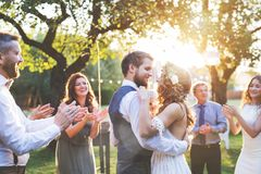 Bride and groom dancing at wedding reception outside in the backyard. Wedding reception outside in the backyard. Bride and groom with a family dancing royalty free stock photo