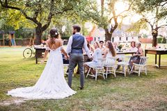 Bride and groom holding hands at wedding reception outside in the backyard. stock images