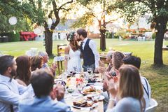 Bride and groom with guests at wedding reception outside in the backyard. Stock Photos