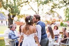 Bride and groom kissing at wedding reception outside in the backyard. royalty free stock photography