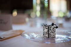 Wedding reception place setting detail. With gift and plate and napkin Royalty Free Stock Photography