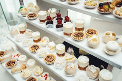 Wedding reception stand with sweets, candies, dessert, cupcakes, muffins, cakes, eclairs decorated with flowers Stock Photo