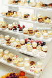 Wedding reception stand with sweets, candies, dessert, cupcakes, muffins, cakes, eclairs decorated with flowers Royalty Free Stock Photography