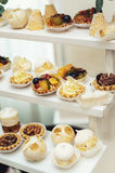 Wedding reception stand with sweets, candies, dessert, cupcakes, muffins, cakes, eclairs decorated with flowers Stock Images